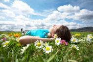 Woman laying in grass looking up at blue sky.