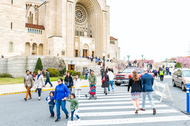 People, families, mothers, and children walking by basilica of the National Shrine of the Immaculate Conception Catholic church street road on Easter Sunday.