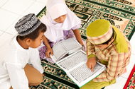 Three children reading the Koran on the floor.