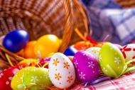 Dozens of colorful Easter eggs pouring out of a basket.
