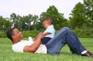 A father and his little son playing on grass.