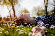 A young girl laying in the grass in the spring sun surrounded by daisies.