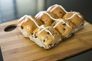 Hot cross buns for Easter on a wooden board.