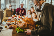 Older man carrying roast turkey to a dinner table. Focus is on man and turkey. Family around the dinner table blurred.