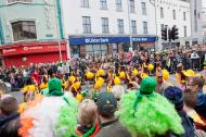 Cheerful people watching St Patrick's day parade in Galway, Ireland.
