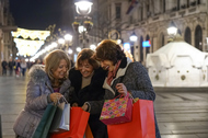 Three older women with shopping bags, smiling while looking into one of the bags. Night time with blurred Christmas lights in the background.