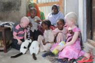 Tanzanian family seated on the floor of their house showing the mother, the aunt and five children, including a son and a daughter with Albinism.